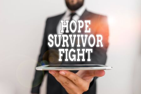 Word writing text Hope Survivor Fight. Business photo showcasing stand against your illness be fighter stick to dreams Male human wear formal work suit hold smart hi tech smartphone use one hand