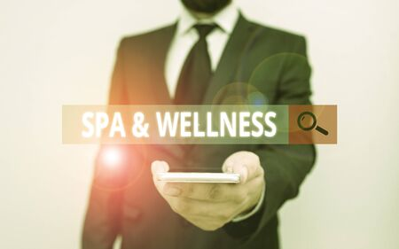 Word writing text Spa And Wellness. Business photo showcasing Place where showing go to improve their health Relaxation Male human wear formal work suit hold smart hi tech smartphone use one hand Фото со стока - 134473497