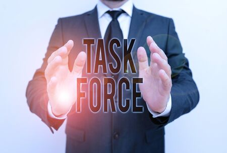 Writing note showing Task Force. Business concept for a group of showing who are brought together to do a particular job Male human with beard wear formal working suit clothes hand
