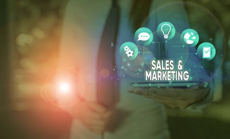Writing note showing Sales And Marketing. Business concept for Promotion Selling Distribution of Goods or Services