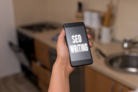 Conceptual hand writing showing Seo Writing. Concept meaning grabbing the attention of the search engines using specific word woman using smartphone and technological devices inside the home
