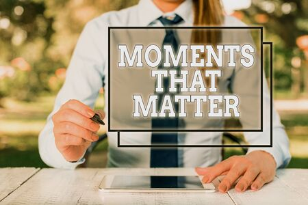 Text sign showing Moments That Matter. Business photo showcasing Meaningful positive happy memorable important times Female business person sitting by table and holding mobile phone Foto de archivo