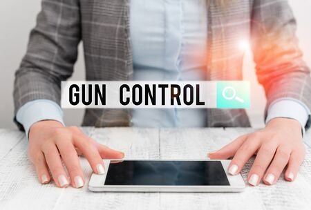Handwriting text Gun Control. Conceptual photo legal measure intended to restrict the possession of guns Business woman sitting with mobile phone on the table