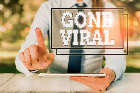 Text sign showing Gone Viral. Business photo text link that spreads rapidly through a population by sharing Female business person sitting by table and holding mobile phone 写真素材