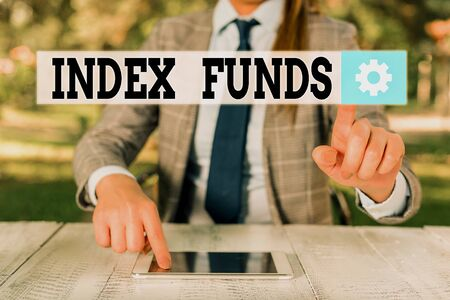 Handwriting text writing Index Funds. Conceptual photo mutual fund built to match the stocks of a market index Female business person sitting by table holding mobile phone