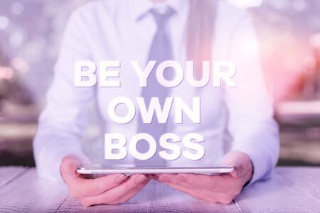 Handwriting text writing Be Your Own Boss. Conceptual photo Entrepreneurship Start business Independence Selfemployed Female business person sitting by table and holding mobile phone Stock fotó