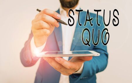 Handwriting text Status Quo. Conceptual photo existing state of affairs regarding social or political issues Businessman pointing with pen in empty copy space Stock Photo