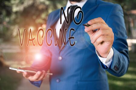 Conceptual hand writing showing No Vaccine. Concept meaning not provided of immunity against one or several diseases Businessman holds laptop and pen pointing into the copy space
