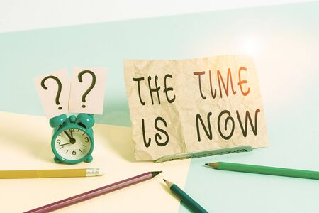 Conceptual hand writing showing The Time Is Now. Concept meaning encouraging someone to start doing today Dont be late Mini size alarm clock beside stationary on pastel backdrop