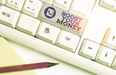 Conceptual hand writing showing Boost Your Money. Concept meaning increase your bank saving using effective methods White pc keyboard with note paper above the white background