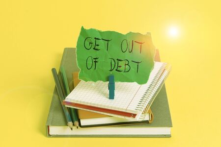 Text sign showing Get Out Of Debt. Business photo showcasing No prospect of being paid any more and free from debt Book pencil rectangle shaped reminder notebook clothespin office supplies