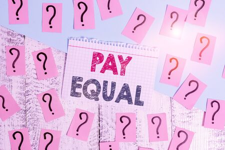 Text sign showing Pay Equal. Business photo showcasing Principle of nondiscrimination in compensation for work Scribbled and crumbling papers with thick cardboard above wooden table