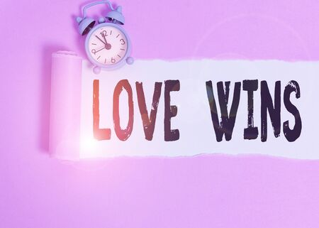 Text sign showing Love Wins. Business photo showcasing used to celebrate or commemorate the victory of marriage equality Alarm clock and torn cardboard placed above plain pastel table backdrop