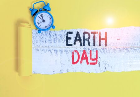 Conceptual hand writing showing Earth Day. Concept meaning Worldwide celebration of ecology environment preservation Alarm clock and torn cardboard on a wooden classic table backdrop