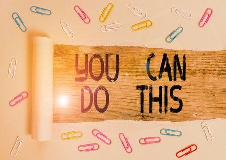 Conceptual hand writing showing You Can Do This. Concept meaning Eagerness and willingness to overcome challenges in life Paper clip and torn cardboard on wood classic table backdrop