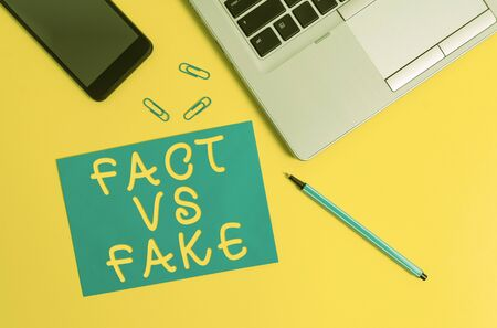 Conceptual hand writing showing Fact Vs Fake. Concept meaning Rivalry or products or information originaly made or imitation Trendy open laptop smartphone marker paper sheet clips 写真素材