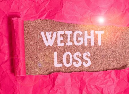 Handwriting text Weight Loss. Conceptual photo the fact of a demonstrating or animals body weight becoming less Cardboard which is torn in the middle placed above a wooden classic table 免版税图像