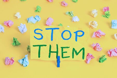 Handwriting text writing Stop Them. Conceptual photo used for telling someone not to do something that they are doing Colored crumpled papers empty reminder white floor background clothespin