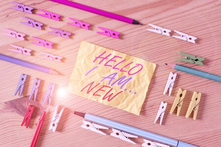 Text sign showing Hello I Am New. Business photo showcasing Introduce yourself Meeting Greeting Work Fresh worker School Colored clothespin papers empty reminder wooden floor background office