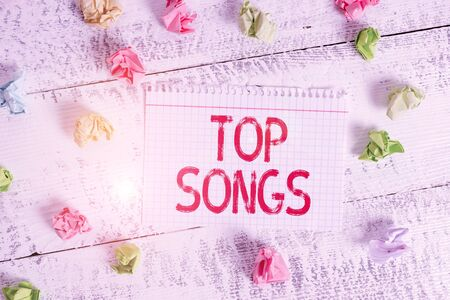 Handwriting text writing Top Songs. Conceptual photo recorded song that becomes broadly popular or wellknown Crumpled colored rectangle square shaped paper reminder white wood desk Zdjęcie Seryjne