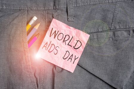 Text sign showing World Aids Day. Business photo text 1st December dedicated to raising awareness of the AIDS Writing equipment and pink note paper inside pocket of man work trousers Archivio Fotografico