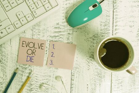 Text sign showing Evolve Or Die. Business photo showcasing Necessity of change grow adapt to continue living Survival technological devices colored reminder paper office supplies keyboard mouse Zdjęcie Seryjne - 134160695