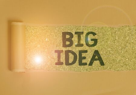 Text sign showing Big Idea. Business photo text Having great creative innovation solution or way of thinking Cardboard which is torn in the middle placed above a wooden classic table