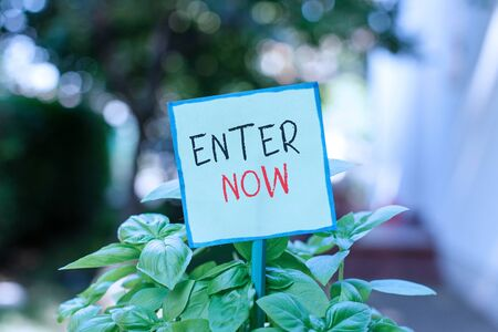 Conceptual hand writing showing Enter Now. Concept meaning come or go into a particular place To be included in a competition Plain paper attached to stick and placed in the grassy land