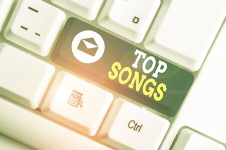 Word writing text Top Songs. Business photo showcasing recorded song that becomes broadly popular or wellknown White pc keyboard with empty note paper above white background key copy space Zdjęcie Seryjne