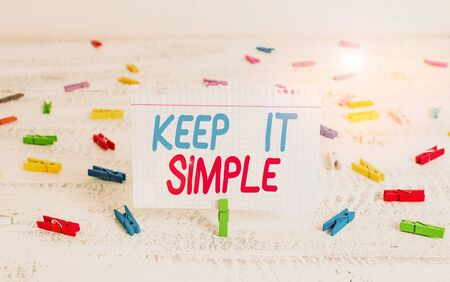 Handwriting text writing Keep It Simple. Conceptual photo Remain in the simple place or position not complicated Green clothespin white wood background colored paper reminder office supply