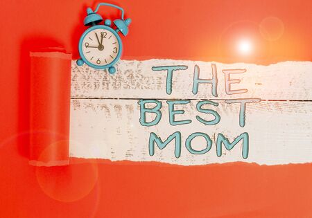 Handwriting text writing The Best Mom. Conceptual photo Appreciation for your mother love feelings compliment Alarm clock and torn cardboard placed above a wooden classic table backdrop