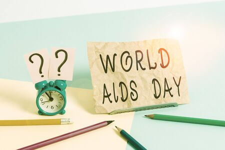 Conceptual hand writing showing World Aids Day. Concept meaning 1st December dedicated to raising awareness of the AIDS Mini size alarm clock beside stationary on pastel backdrop Archivio Fotografico