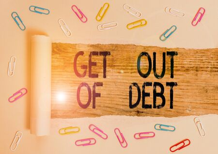 Conceptual hand writing showing Get Out Of Debt. Concept meaning No prospect of being paid any more and free from debt Paper clip and torn cardboard on wood classic table backdrop