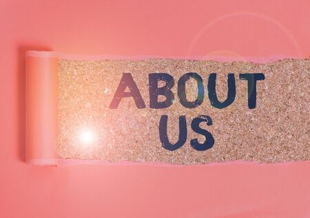 Text sign showing About Us. Business photo text to introduce who or what something relates to or concerns Cardboard which is torn in the middle placed above a wooden classic table