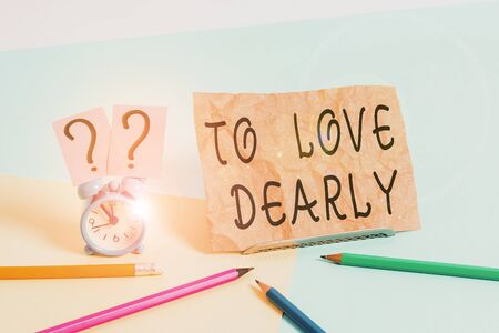Conceptual hand writing showing To Love Dearly. Concept meaning Love someone very much in the more humble way and aimlessly Mini size alarm clock beside stationary on pastel backdrop