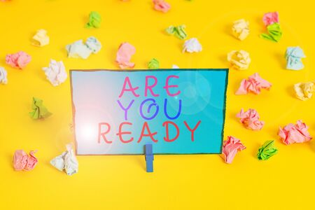 Text sign showing Are You Ready. Business photo showcasing Alertness Preparedness Urgency Game Start Hurry Wide awake Colored crumpled papers empty reminder white floor background clothespin