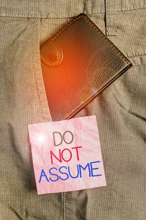Text sign showing Do Not Assume. Business photo text Ask first to avoid misunderstandings confusion problems Small little wallet inside man trousers front pocket near notation paper