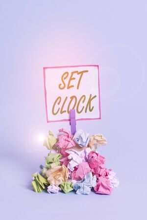 Handwriting text Set Clock. Conceptual photo put it to the right time or change the clock time to a later time Reminder pile colored crumpled paper clothespin reminder blue background