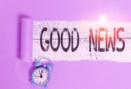 Word writing text Good News. Business photo showcasing Someone or something positive Encouraging uplifting or desirable Alarm clock and torn cardboard placed above a wooden classic table backdrop