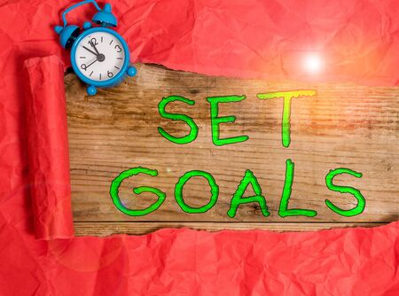 Writing note showing Set Goals. Business concept for Defining or achieving something in the future based on plan Alarm clock and torn cardboard on a wooden classic table backdrop
