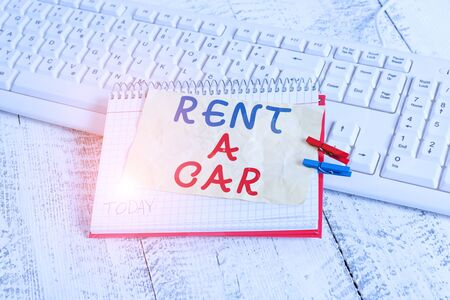 Conceptual hand writing showing Rent A Car. Concept meaning paying for temporary vehicle usage from one day to months notebook reminder clothespin with pinned sheet light wooden