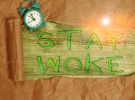 Writing note showing Stay Woke. Business concept for being aware of your surroundings and things going on Keep informed Alarm clock and torn cardboard on a wooden classic table backdrop Stock Photo