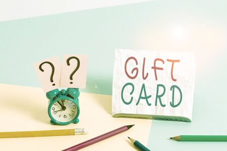 Writing note showing Gift Card. Business concept for A present usually made of paper that contains your message Mini size alarm clock beside stationary on pastel backdrop