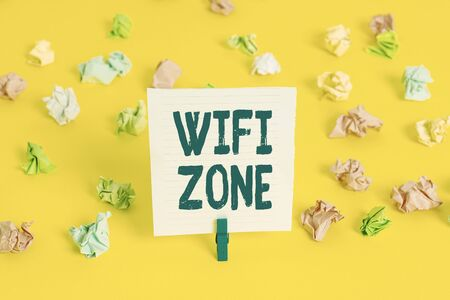 Word writing text Wifi Zone. Business photo showcasing provide wireless highspeed Internet and network connections Colored crumpled papers empty reminder white floor background clothespin Banque d'images