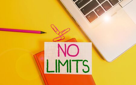 Writing note showing No Limits. Business concept for to do whatever you could with out restrictions and holding back Laptop clips pencil paper sheet hard cover notebook colored background