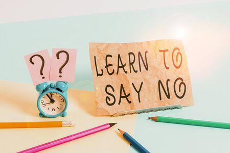 Conceptual hand writing showing Learn To Say No. Concept meaning dont hesitate tell that you dont or want doing something Mini size alarm clock beside stationary on pastel backdrop