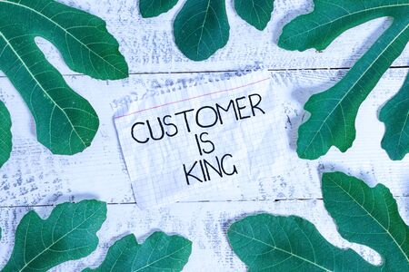 Writing note showing Customer Is King. Business concept for Serve attentively and properly Deliver the needs urgently Leaves surrounding notepaper above a classic wooden table