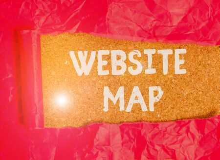 Handwriting text Website Map. Conceptual photo designed to help both users and search engines navigate the site Cardboard which is torn in the middle placed above a wooden classic table