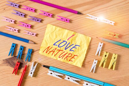 Text sign showing I Love Nature. Business photo showcasing Enjoy the natural environment Preservation Protect ecosystem Colored clothespin papers empty reminder wooden floor background office Banco de Imagens