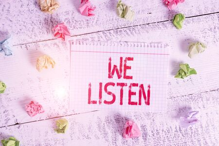 Handwriting text writing We Listen. Conceptual photo Group of showing that is willing to hear anything you want to say Crumpled colored rectangle square shaped paper reminder white wood desk